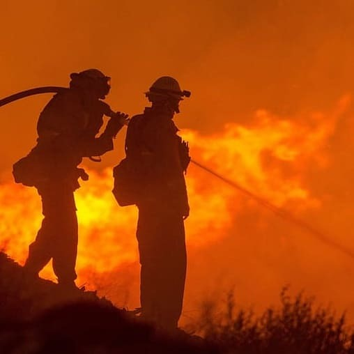 Silhouette of two firefighers
